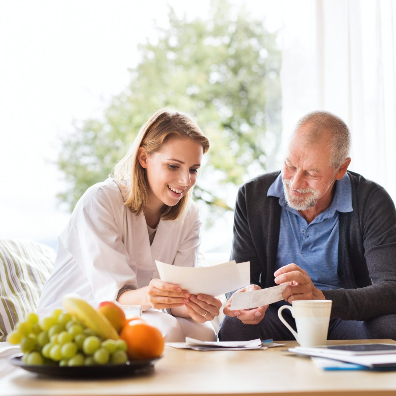 health-visitor-and-a-senior-man-with-tablet-during-home-visit-.jpg